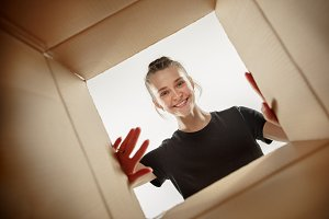 Woman unpacking and opening carton