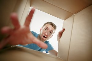 Man smiling, unpacking and opening