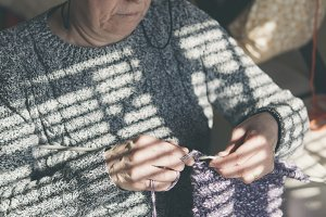 woman sitting on settee knitting
