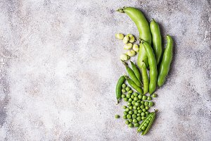 Fresh green peas and beans on light