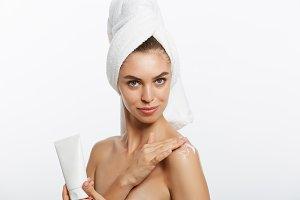 Woman applying cream on shoulder on