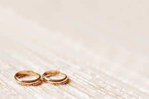 Golden wedding rings on beige fabric