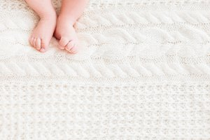 Baby's feet on white knitted fabric