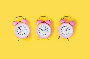 Three Pink alarm clocks
