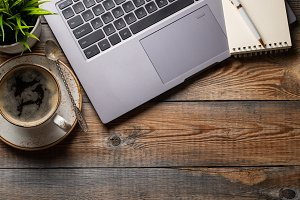 Desk with laptop, eye glasses, notep