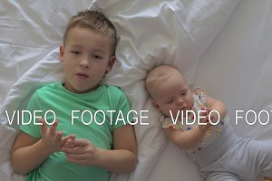 Boy and baby girl siblings on bed at
