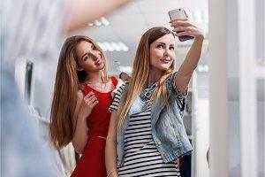 Two smiling girls taking selfie