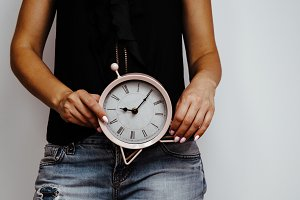 Woman is holding a pink clock