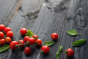 Red cherry tomatoes on black wooden