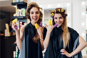 Two girls curling hair with curlers