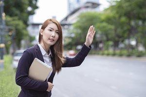 Businesswoman hailing a taxi cab hol
