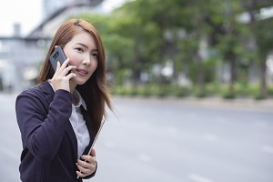 Businesswoman hailing a taxi cab whi