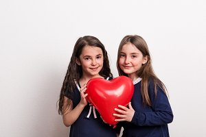 Two small girls in a studio, holding