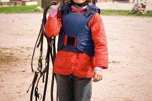 Little girl riding a horse.