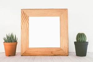 Wooden frames with cactus on table
