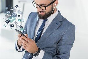 businessman in earphones using smart