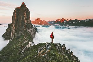 Traveler on cliff over clouds