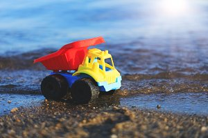 Toy truck on the gold sandy beach