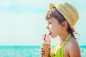 the child eats ice cream on the sea.
