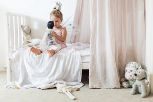 little girl playing dolls in bedroom