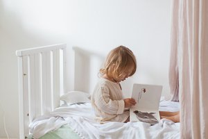 Little girl reading in bedroom