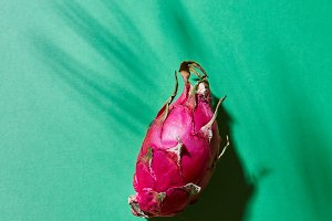 Pink pitahaya on a green background