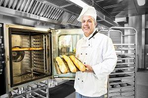 Proud mature baker showing baguettes