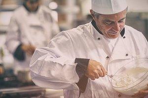Happy chef whisking cream