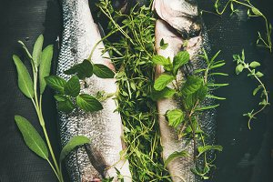 Raw uncooked sea bass with herbs on