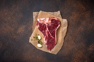 Raw T-bone steak with garlic and