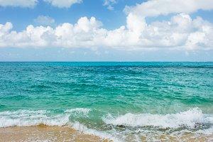 Blue sea water cloudy sky sand beach