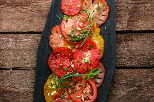 Sliced tomatoes on a black wooden