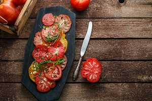 Colored sliced tomatoes on a black