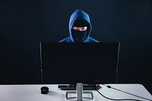 Unrecognizable masked man under hood