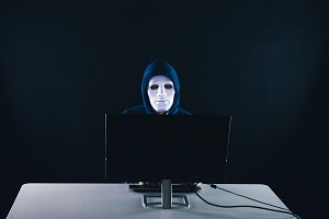 Anonymous and masked hacker under ho