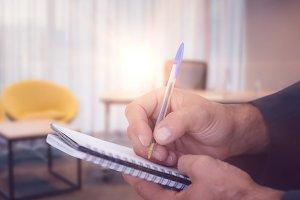 Man writing in spiral book