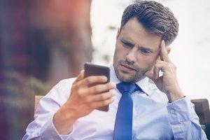 Tensed businessman using phone