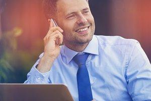 Cheerful businessman talking phone