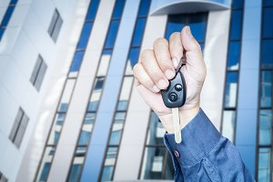 Hand holding car key on building