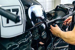 Motorcycle mechanic changing a fuse