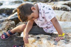 Little kid looking a snail
