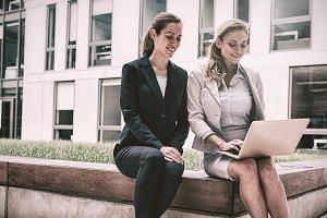 Businesswomen sitting, using laptop