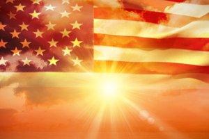Waving American flag against sunrise