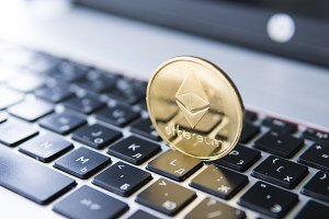 Gold Ethereum coin on a laptop