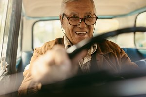 Happy old man enjoying driving