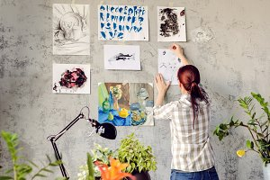 The artist hangs work on wall.