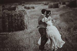 bride and groom near hay barn