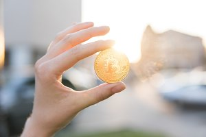 Golden bitcoin coin in hand on a