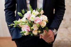 Pink pastel bouquet in grooms hands