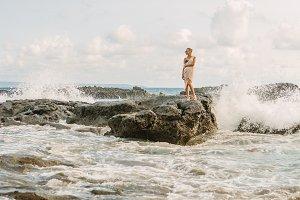 Pretty woman near danger rocks on oc